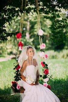 Bela noiva balançando em um balanço