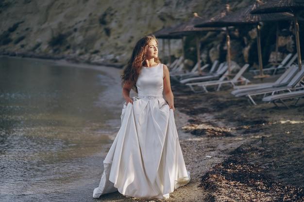 Bela noiva de cabelos compridos em um magnífico vestido branco caminhando na praia