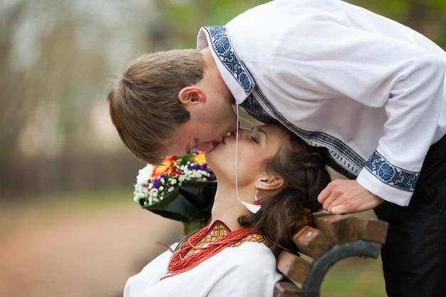 Bela noiva e noivo ucraniano em trajes de bordado nativos beijando em um banco no fundo de árvores em um parque