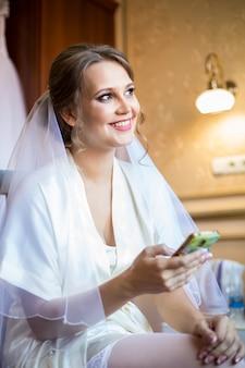 Bela noiva sexy em lingerie e véu, olhando para o celular enquanto está sentado em uma cadeira
