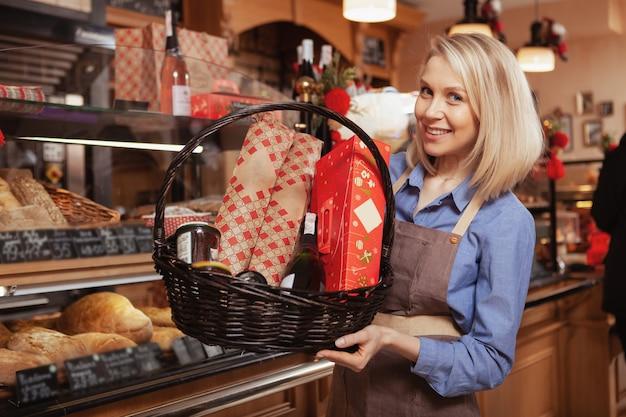Bela padeiro feminino sorrindo, segurando uma grande cesta cheia de comida, vendida em sua loja.