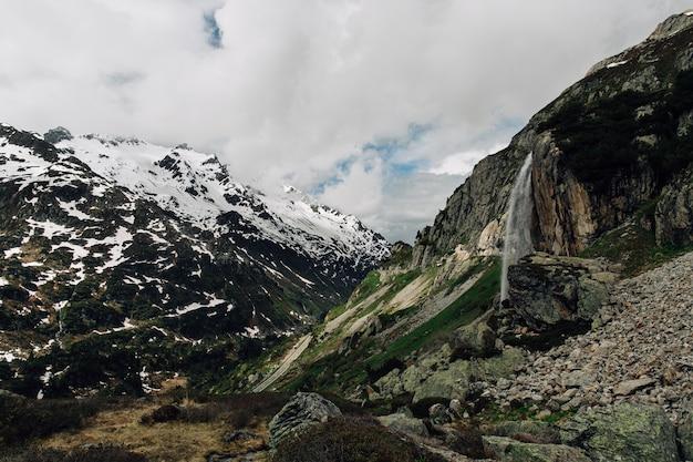Bela paisagem alpina com cascata na montanha no horário de verão