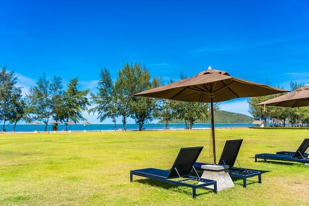 Bela paisagem ao ar livre do mar e praia com guarda-chuva e cadeira