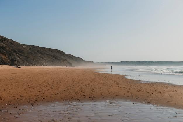 Bela paisagem ao pôr do sol em portugal, bordeira praia com uma pessoa caminhando à beira-mar.