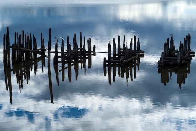 Bela paisagem aquática com fragmentos de pilhas de pontes destruídas que lembram hieróglifos desconhecidos