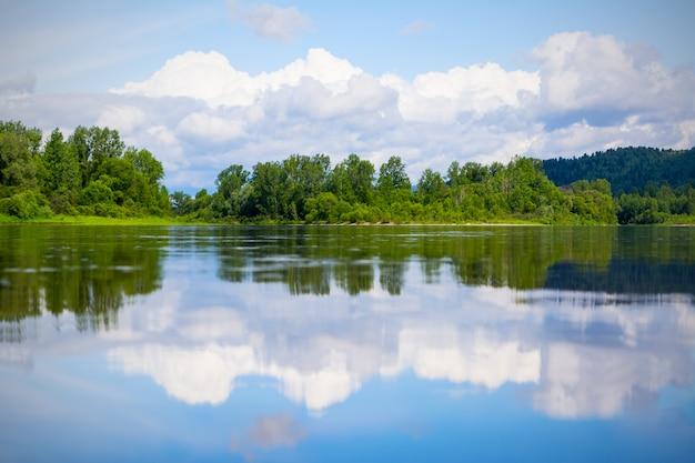 Bela paisagem com céu azul e nuvens brancas refletidas na água do rio claro