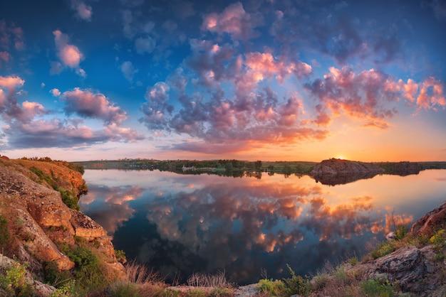 Bela paisagem com céu nublado colorido, lago e montanhas