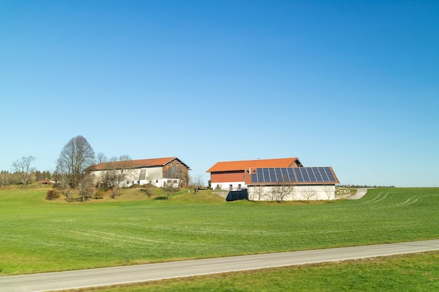 Bela paisagem com edifícios de agricultura com painéis solares em um telhado em campos verdes e áreas em um fundo de céu azul limpo em um tempo de outono, na áustria.