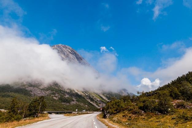 Bela paisagem com estrada sinuosa nas montanhas com nuvens