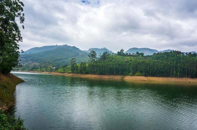 Bela paisagem com lago de montanha em meio a altas montanhas com plantações de chá e céu nublado. munnar kerala india.