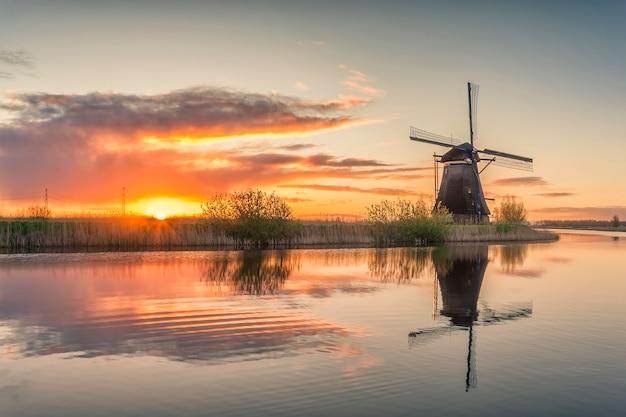 Bela paisagem com moinhos de vento e reflexo majestoso do céu na água