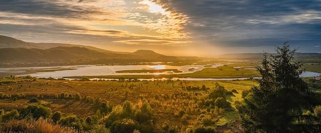 Bela paisagem com montanhas e colinas, rios e árvores iluminadas pelos raios do sol nascente por entre as nuvens no céu. protetor de tela, layout, maquete, conceito natural.