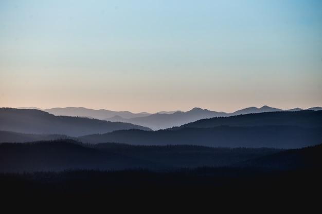 Bela paisagem com montanhas e colinas sob um céu rosado