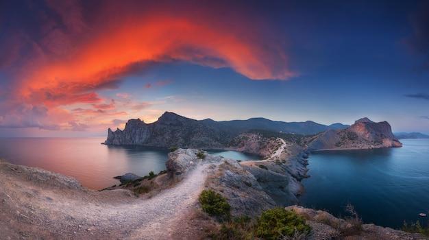 Bela paisagem com montanhas, mar ao pôr do sol