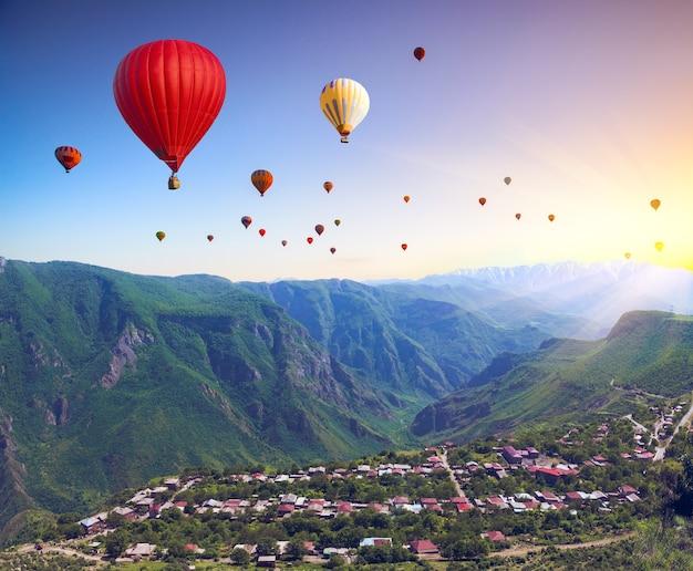 Bela paisagem com montanhas verdes e balões de ar