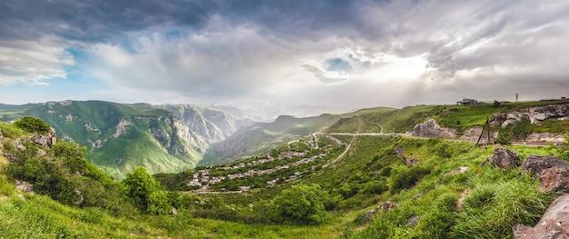 Bela paisagem com montanhas verdes e um magnífico céu nublado ao pôr do sol