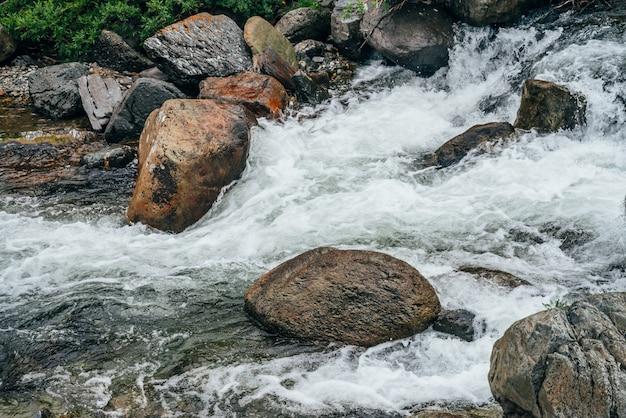Bela paisagem com pedras grandes no riffle de água do rio da montanha. fluxo de água poderoso entre pedregulhos no riacho de montanha com corredeiras. fluxo rápido entre rochas no ribeiro das montanhas. rio pequeno close-up