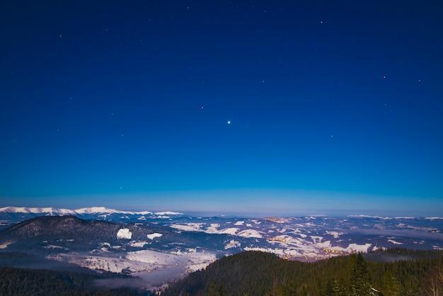 Bela paisagem com pinheiros altos e majestosos crescendo entre montes de neve branca contra o céu azul em um dia ensolarado de inverno gelado