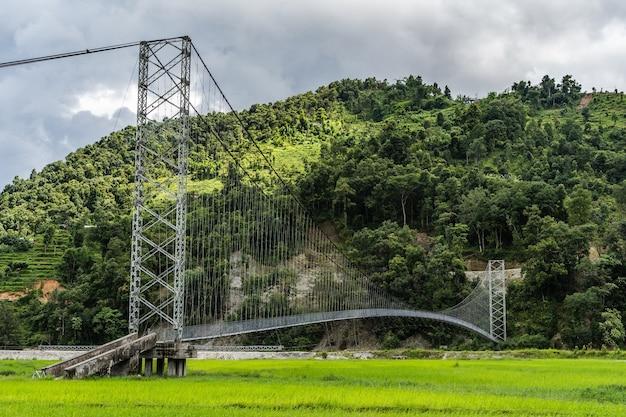 Bela paisagem com ponte pênsil para pedestres, campo de arroz e montanhas cobertas de selva.