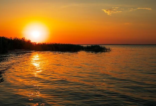 Bela paisagem com pôr do sol. céu colorido. costa do reservatório, ondas.