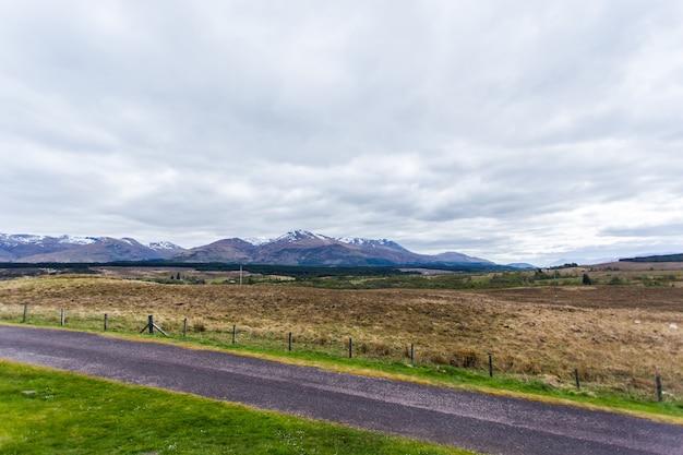 Bela paisagem com uma estrada e altas montanhas cobertas de neve brilhando sob o céu nublado
