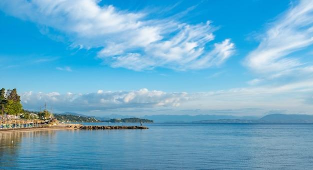 Bela paisagem da praia do mar jônico com espreguiçadeiras coloridas, árvores e hotéis para turistas