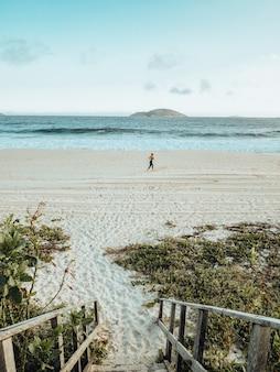 Bela paisagem da praia durante o pôr do sol com uma pessoa se exercitando