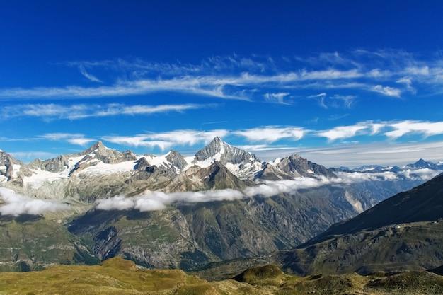 Bela paisagem de alpes suíços com montanha nas nuvens vista no verão
