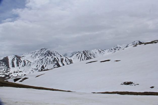 Bela paisagem de altas montanhas rochosas cobertas de neve sob um céu nublado