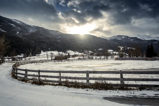 Bela paisagem de fazenda com cerca de madeira na cidade austríaca de terras altas ao pôr do sol