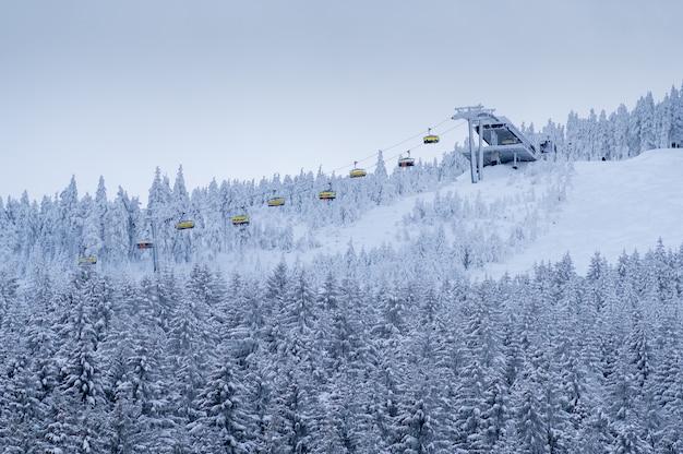 Bela paisagem de floresta de montanha de inverno com pessoas levantando em um teleférico