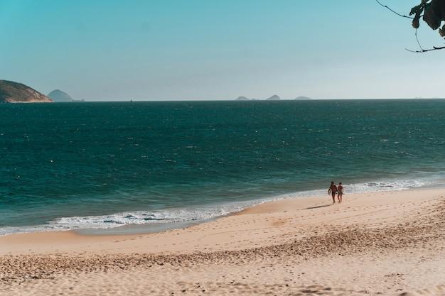 Bela paisagem de gente caminhando na praia do rio de janeiro