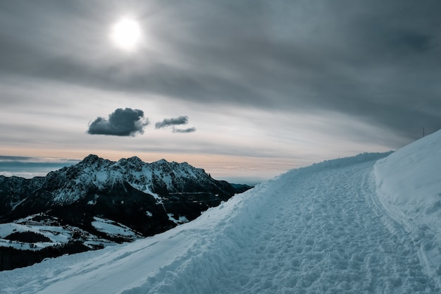 Bela paisagem de inverno com um caminho de neve e uma bela vista das montanhas cobertas de neve
