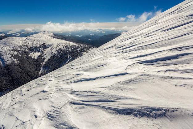 Bela paisagem de inverno. encosta íngreme do morro da montanha com neve branca profunda, panorama distante da cordilheira arborizada que se estende até o horizonte e os raios de sol brilhantes no fundo do espaço da cópia do céu azul.