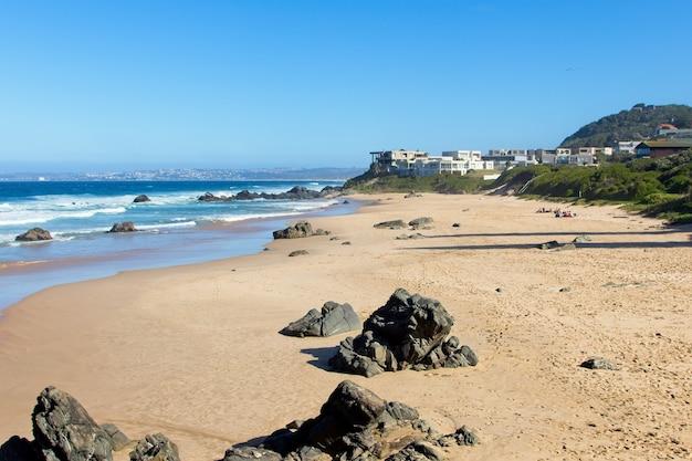 Bela paisagem de praia cercada por morros e céu claro