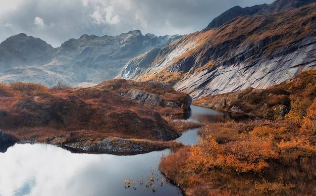 Bela paisagem de queda de montanha com um lago, o sol ilumina uma rocha molhada após a chuva contra um céu tempestuoso