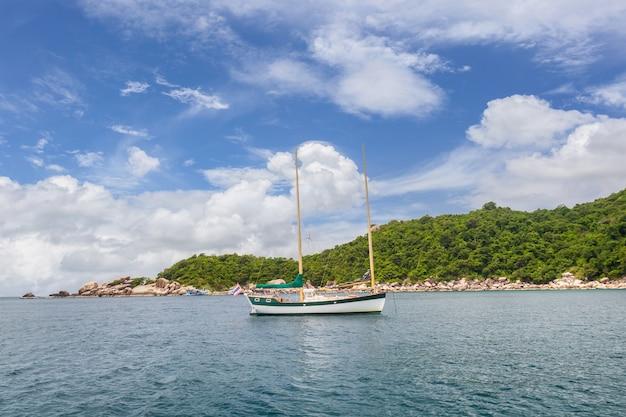 Bela paisagem de um barco navegando e vegetação nas montanhas em um dia ensolarado na tailândia