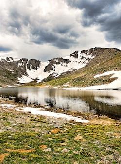 Bela paisagem de um lago cercado por altas montanhas rochosas cobertas de neve sob um céu nublado