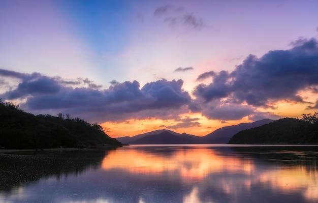 Bela paisagem de um lago cercado por montanhas arborizadas sob um céu roxo ao pôr do sol
