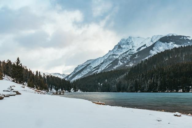 Bela paisagem de um lago rodeado por altas montanhas rochosas cobertas de neve sob o sol
