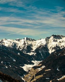 Bela paisagem de uma cadeia de montanhas rochosas cobertas de neve sob um céu nublado