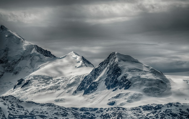 Bela paisagem de uma cordilheira coberta de neve sob o céu nublado