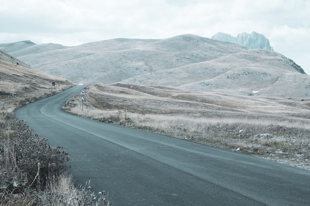 Bela paisagem de uma estrada de colinas em um dia nublado