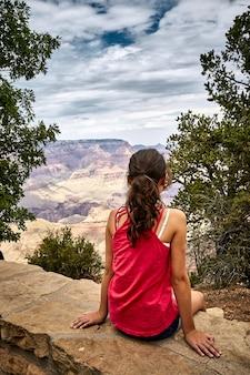 Bela paisagem de uma jovem sentada no parque nacional do grand canyon, arizona - eua