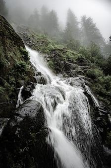 Bela paisagem de uma poderosa cachoeira cercada por penhascos rochosos e árvores no canadá