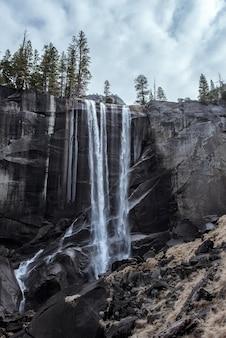 Bela paisagem de uma poderosa cachoeira fluindo por um penhasco rochoso sob um céu nublado