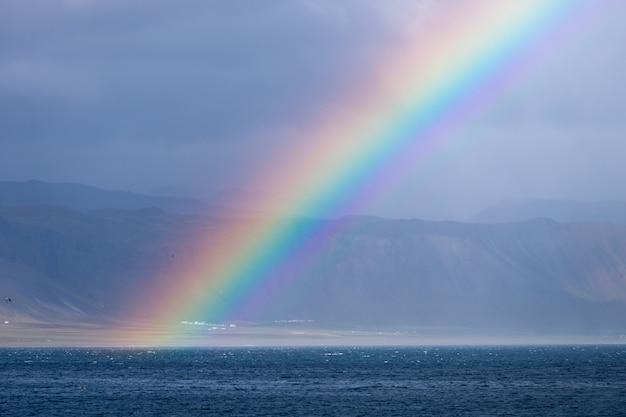 Bela paisagem de verão com mar, pequena vila na colina, arco-íris colorido brilhante no céu azul, nuvens e montanhas no horizonte, península da islândia