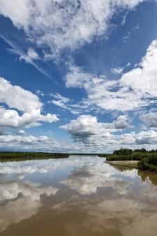 Bela paisagem de verão: vista sobre o rio kamchatka, belas nuvens e reflexo na água. extremo oriente russo, península de kamchatka.