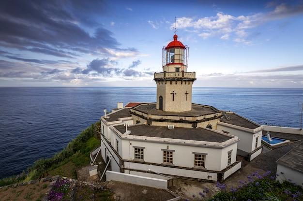 Bela paisagem do farol da ponta do arnel com o mar ao fundo Foto Premium