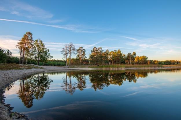 Bela paisagem do lago ao pôr do sol colorido. árvores refletindo na água